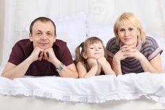 Glücklicher Vater, kleine Tochter und Mutter auf weißem Bett Stockfotos