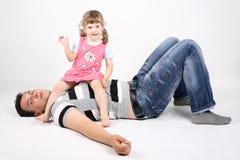 Glücklicher Vater liegt auf Boden und kleine Tochter sitzt Lizenzfreie Stockbilder