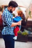 Glücklicher Vater mit Baby im Riemenrucksack, der einen Weg in der Stadt hat Stockfotografie