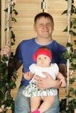 Glücklicher Vater mit nettem Baby sitzt auf Schwingen Stockbild