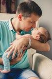 Glücklicher Vater mit seinem neugeborenen Sohn zu Hause Stockfotografie