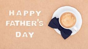 Glücklicher Vater ` s Tageshintergrund Tasse Kaffee und schwarze Fliege auf brauner Hintergrundebenenlage Dieses ist Datei des Fo Stockbilder