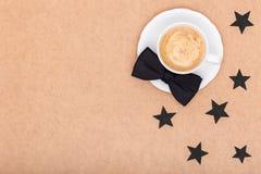 Glücklicher Vater ` s Tageshintergrund Tasse Kaffee und schwarze Fliege auf brauner Hintergrundebenenlage Dieses ist Datei des Fo Lizenzfreies Stockfoto