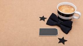 Glücklicher Vater ` s Tageshintergrund Tasse Kaffee und schwarze Fliege auf brauner Hintergrundebenenlage Dieses ist Datei des Fo Stockbild
