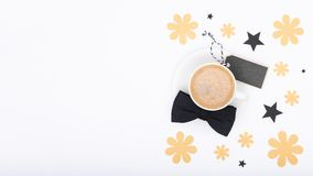 Glücklicher Vater ` s Tageshintergrund Tasse Kaffee und schwarze Fliege auf weißer Hintergrundebenenlage Blumenvatertagsstilllebe Stockfotografie