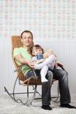 Glücklicher Vater sitzt mit kleiner Tochter im Schaukelstuhl Stockfoto