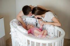 Glücklicher Vater und Mutter, die herein nettes kleines neugeborenes Baby einschläfert stockfotos