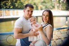 Glücklicher Vater und Mutter, die mit nettem Baby im Park geht lizenzfreie stockbilder