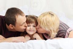 Glücklicher Vater und Mutter liegen auf Bett und küssen wenig Stockbild