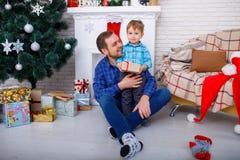 Glücklicher Vater und sein Sohn zu Hause nahe einem Weihnachtsbaum mit einem Geschenk stockfotografie