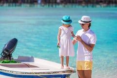 Glücklicher Vater und seine entzückende kleine Tochter am tropischen Strand, der Spaß hat Lizenzfreie Stockbilder