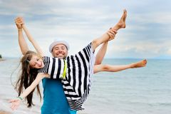 Glücklicher Vater und seine Tochter am Strand lizenzfreie stockbilder