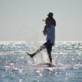 Glücklicher Vater und Sohn auf dem Küstenstrand, der Spaßwasserspritzen hat Lizenzfreie Stockbilder
