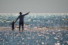 Glücklicher Vater und Sohn auf Küste setzen Haben des Spaßes auf den Strand  Lizenzfreies Stockbild