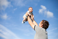 Glücklicher Vater und Sohn, die auf Himmel spielt Stockfoto