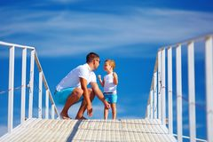 Glücklicher Vater und Sohn, die auf Horizont des blauen Himmels spielt lizenzfreies stockfoto