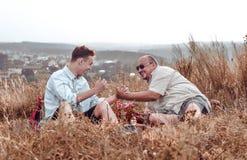 Glücklicher Vater und Sohn, die auf Natur am Abend stillsteht stockbilder