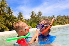 Glücklicher Vater und Sohn, die auf Strand schnorchelt Stockbild