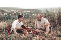 Glücklicher Vater und Sohn, die einen Rest auf Natur an einem Sommertag hat lizenzfreies stockfoto