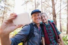 Glücklicher Vater und Sohn, die selfie vom Handy nimmt Stockbilder
