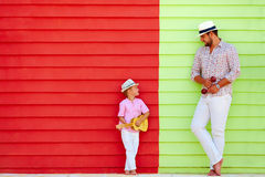Glücklicher Vater und Sohn mit Musikinstrumenten nahe der bunten Wand Lizenzfreies Stockbild