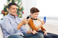 Glücklicher Vater und Sohn mit Smartphones am Weihnachten Stockfotografie