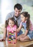 Glücklicher Vater und Töchter, die mit Abakus im Haus spielen Stockfotos