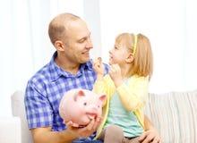 Glücklicher Vater und Tochter mit großem Sparschwein Stockbild