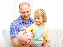 Glücklicher Vater und Tochter mit großem Sparschwein Lizenzfreies Stockfoto