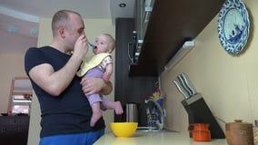 Glücklicher Vatermannzufuhr-Babysohn mit Löffel in der Küche 4K stock video footage