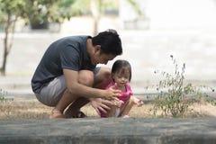 Glücklicher Vatertagelöhner und seine Tochter, die am Park mit wenigem Mädchen zeigt ihrem Vater etwas am sonnigen Tag spielt stockfotografie