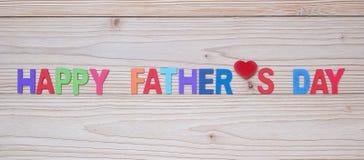 Glücklicher Vatertagstext mit roter Herzform auf hölzernem Hintergrund Internationale Konzepte der M?nner Tages lizenzfreie abbildung