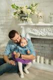 Glücklicher Vati mit einer kleinen Tochter in den Jeanskleidern Lizenzfreies Stockfoto