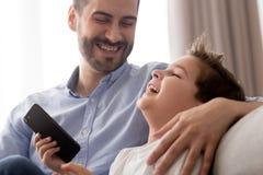 Gl?cklicher Vati und kleines Sohnlachen unter Verwendung des Smartphone zu Hause lizenzfreie stockfotos