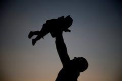 Glücklicher Vati wirft das Baby bei Sonnenuntergang Lizenzfreie Stockfotos