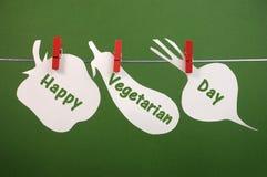 Glücklicher vegetarischer Tagesmitteilungsgruß geschrieben über die Gemüsekarten, die von den Klammern auf eine Linie hängen Lizenzfreies Stockfoto