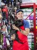 Glücklicher Verkäufer Carrying French Bulldog im Haustier-Speicher Stockbilder