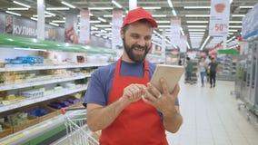 Glücklicher Verkäufer, der eine digitale Tablette im Supermarkt verwendet stock footage