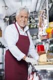 Glücklicher Verkäufer Standing At Counter im Käse-Shop Stockbilder