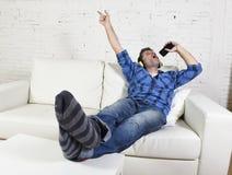 Glücklicher verrückter Mann auf Couch hörend Musik, die Handy als Mikrofon hält Lizenzfreie Stockfotografie