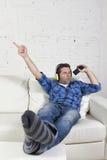 Glücklicher verrückter Mann auf Couch hörend Musik, die Handy als Mikrofon hält Stockbild
