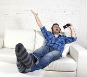 Glücklicher verrückter Mann auf Couch hörend Musik, die Handy als Mikrofon hält Stockfotografie