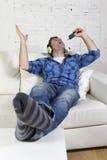 Glücklicher verrückter Mann auf Couch hörend Musik, die Handy als Mikrofon hält Lizenzfreies Stockfoto