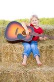 Glücklicher Vorschüler, der die Gitarre spielt. Stockfoto