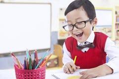 Glücklicher Vorschülerabgehobener betrag mit Farbbleistiften Lizenzfreies Stockfoto