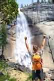 Glücklicher wandernder Mann, der im Erfolg durch Wasserfall zujubelt stockbild