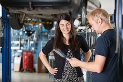 Glücklicher weiblicher Abnehmer am Mechaniker Lizenzfreie Stockbilder