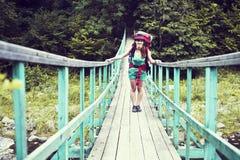 Glücklicher weiblicher Bergsteiger, der auf einer Holzbrücke über einem Gebirgsstrom überläuft mit Aufregung mit dem Ruhm und der Stockfoto