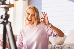 Glücklicher weiblicher Blogger, der positiv gestikuliert Stockfotos
