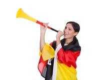 Glücklicher weiblicher deutscher Anhänger, der Vuvuzela durchbrennt Lizenzfreies Stockfoto